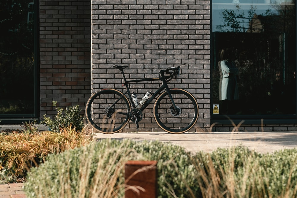 black and gray mountain bike beside brown brick wall