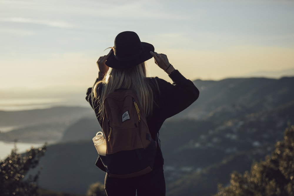 woman in gray hoodie and black pants wearing black hat standing on top of mountain during