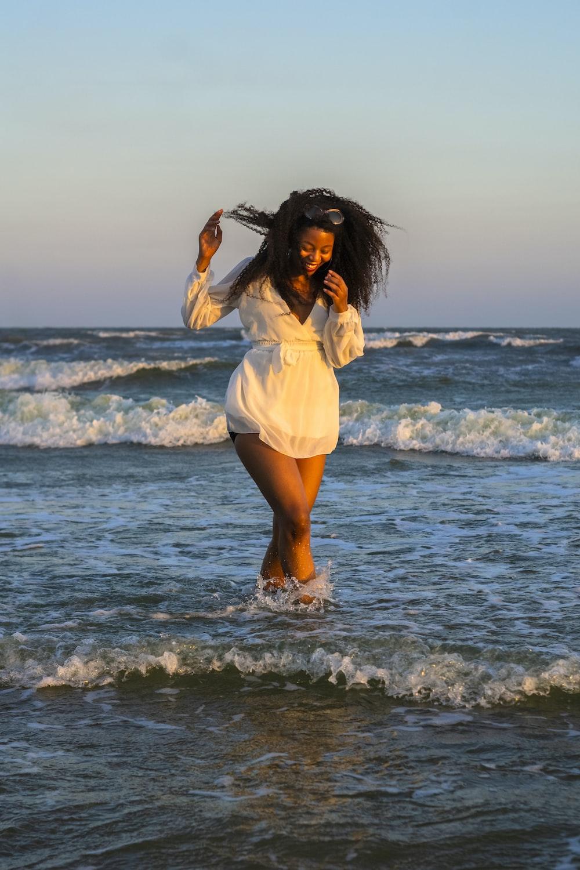 woman in white dress shirt standing on seashore during daytime