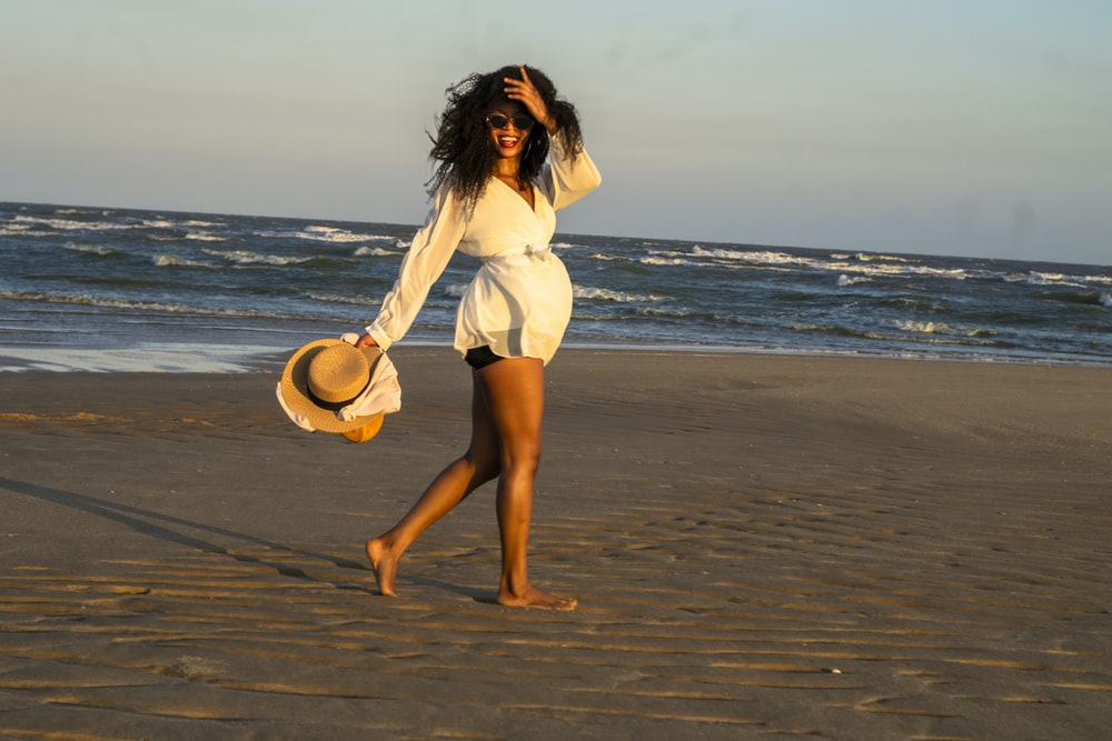 woman in white dress holding brown hat standing on beach during daytime