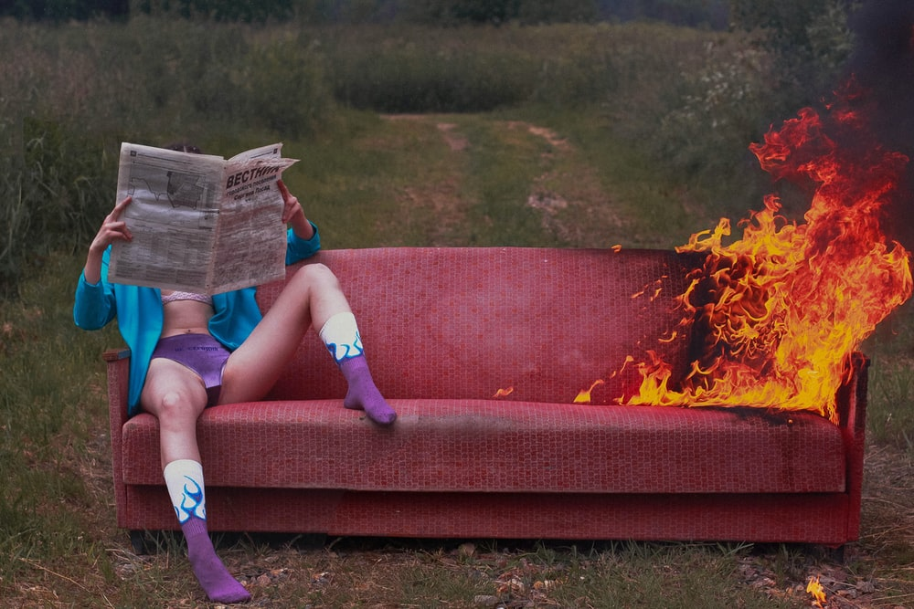 woman in blue denim shorts lying on red couch