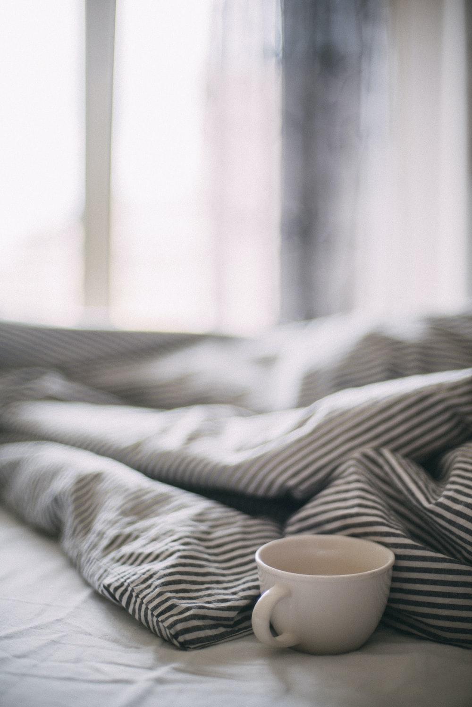 white ceramic mug on white and black zebra print textile