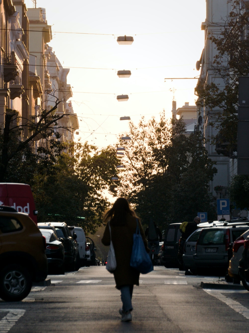 woman in black jacket standing on sidewalk during daytime