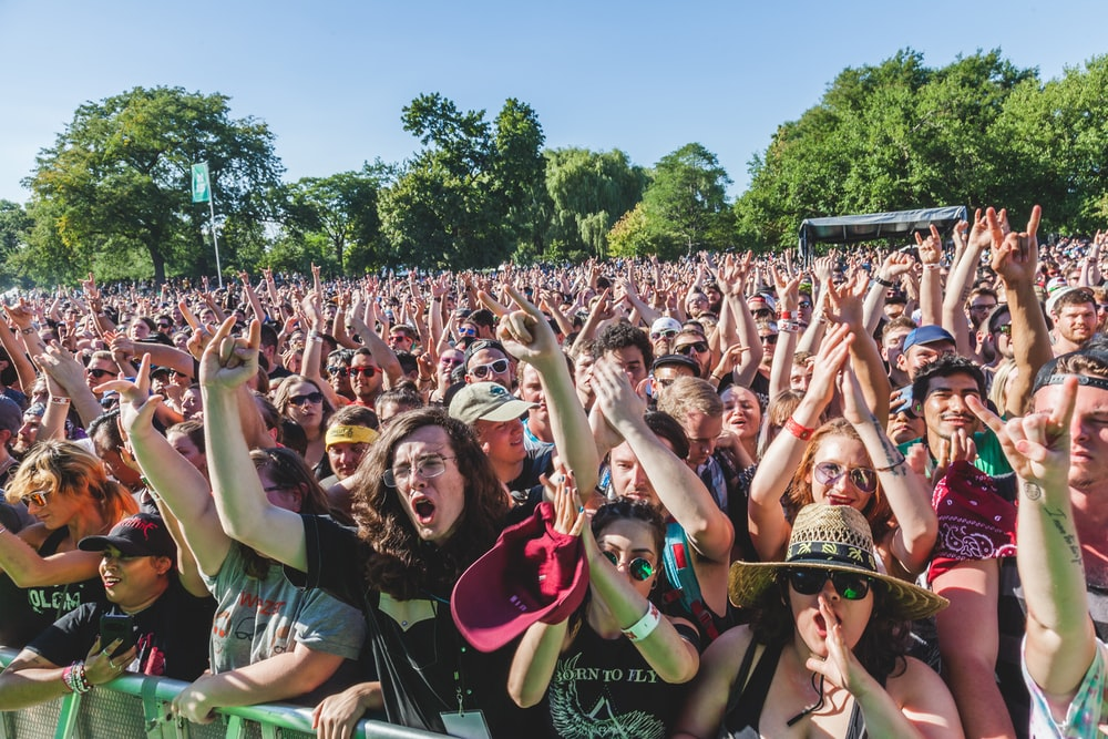 group of people raising their hands during daytime
