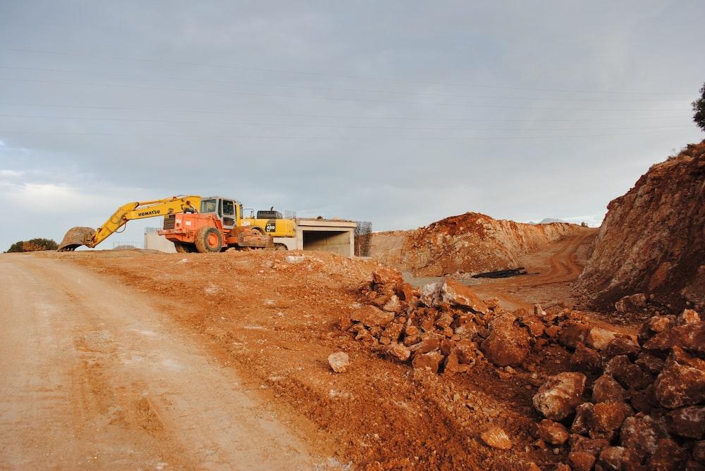yellow excavator near brown rock formation during daytime