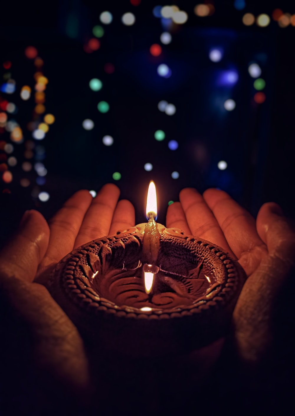 lighted candle on brown round holder