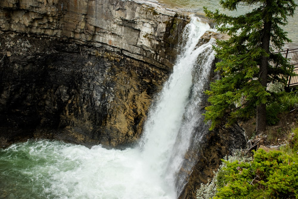 waterfalls between brown rocky mountain during daytime