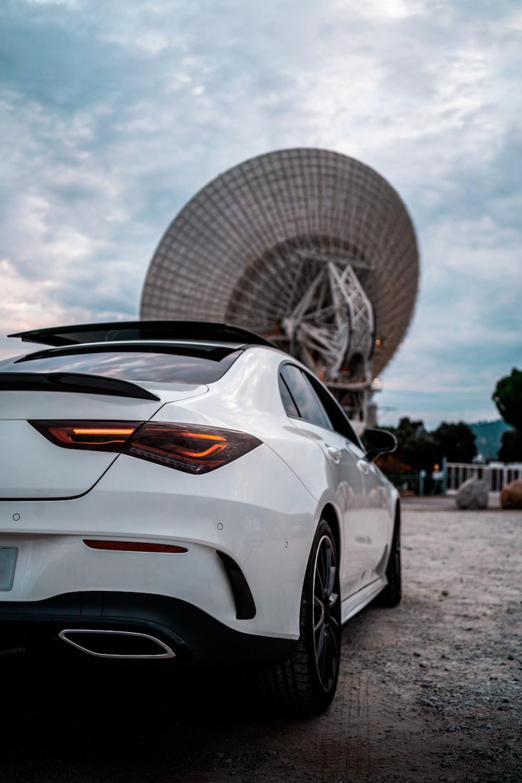 white porsche 911 parked near white ferris wheel during daytime