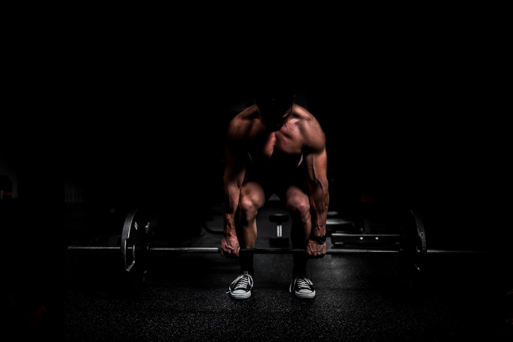 topless man in black shorts sitting on black and silver barbell