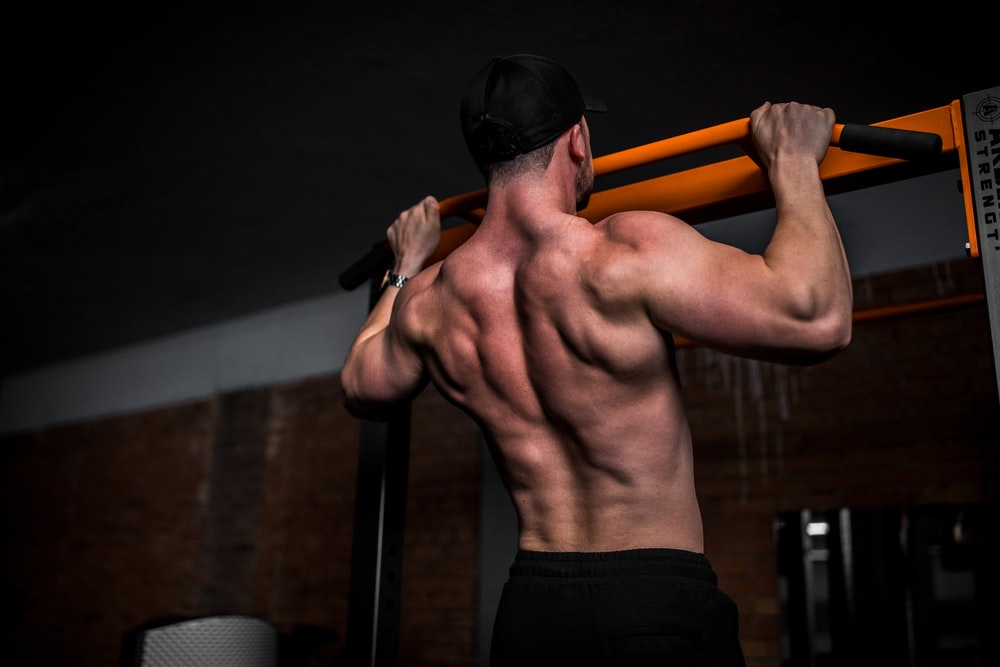 topless man in black shorts holding orange bar