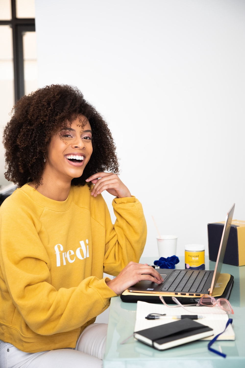 woman in yellow sweater sitting beside table with laptop computer
