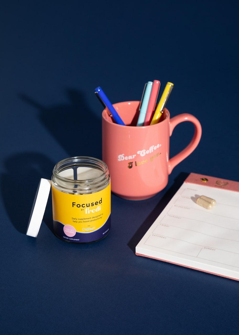 red ceramic mug with pens and pencils