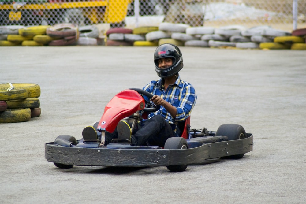 man in red and black racing suit riding go kart