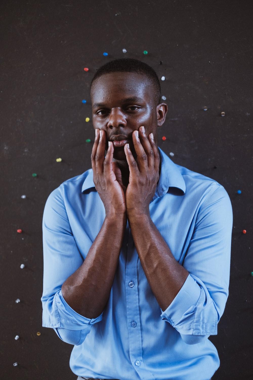 man in blue dress shirt smoking cigarette