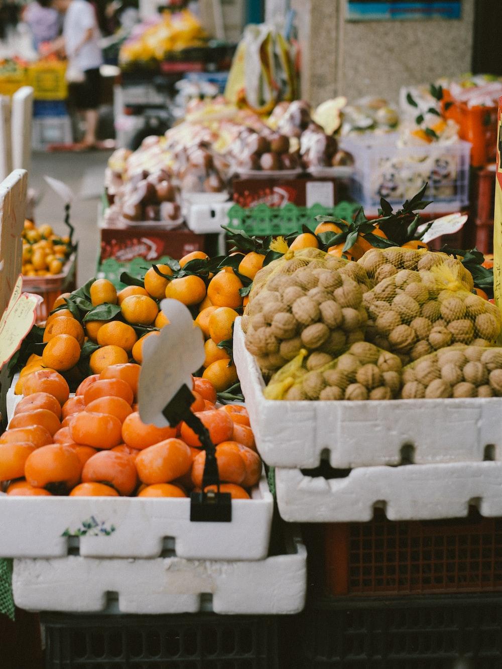orange fruits on white plastic crate