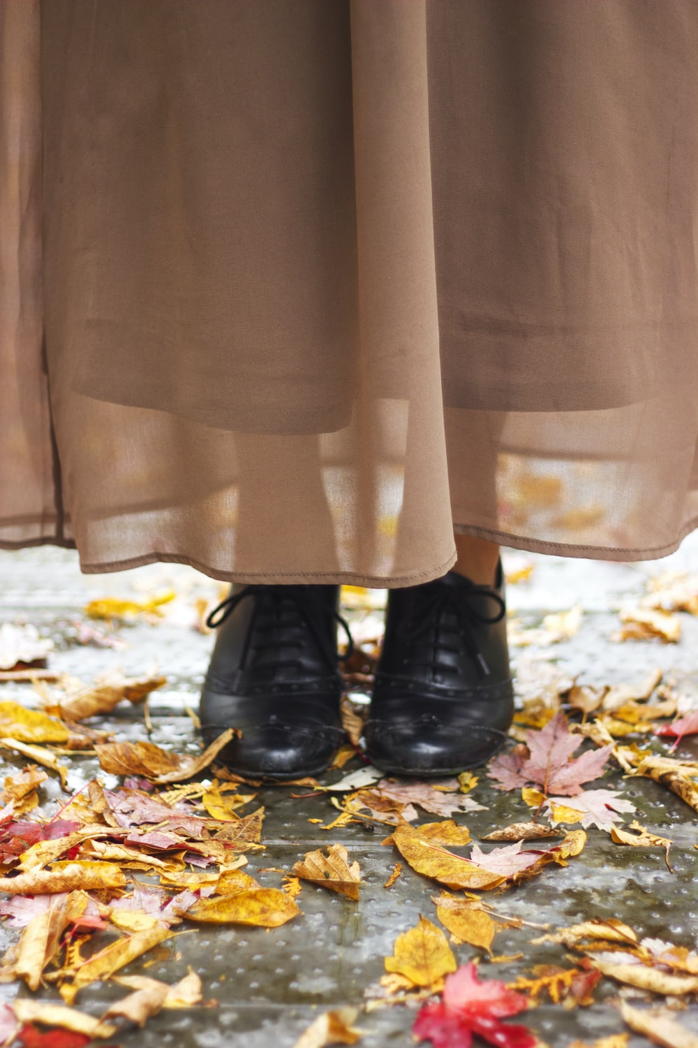 person in black leather boots standing on dried leaves