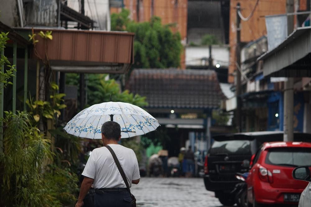 man in black shirt holding umbrella walking on street during daytime