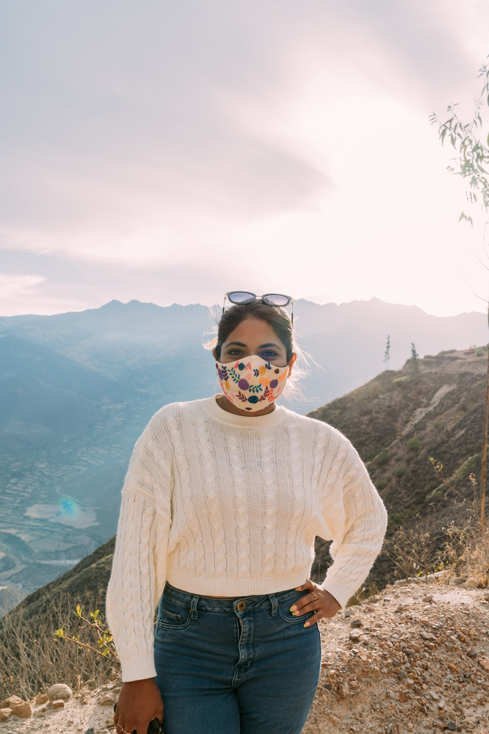 man in white sweater standing on mountain during daytime