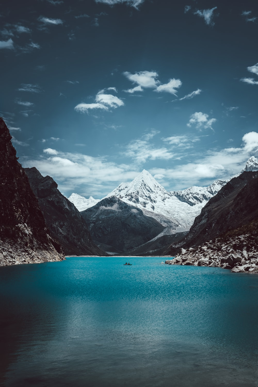 lake in the middle of mountains under blue sky