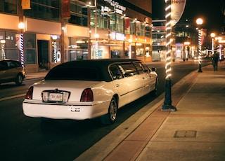 white sedan parked on sidewalk during night time
