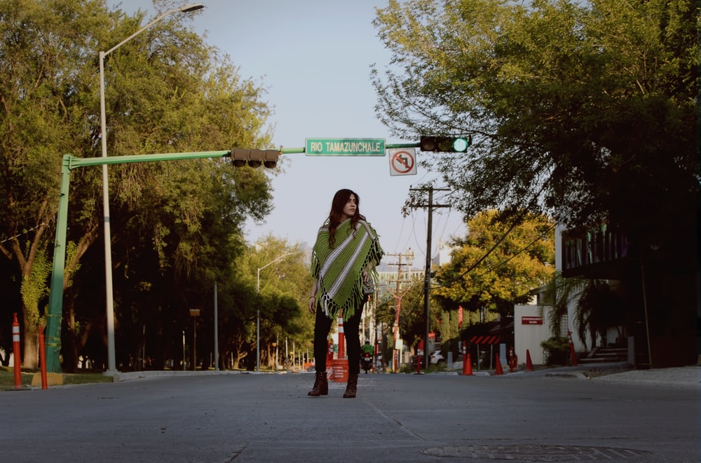 woman in green and white stripe long sleeve shirt and red pants standing on street during