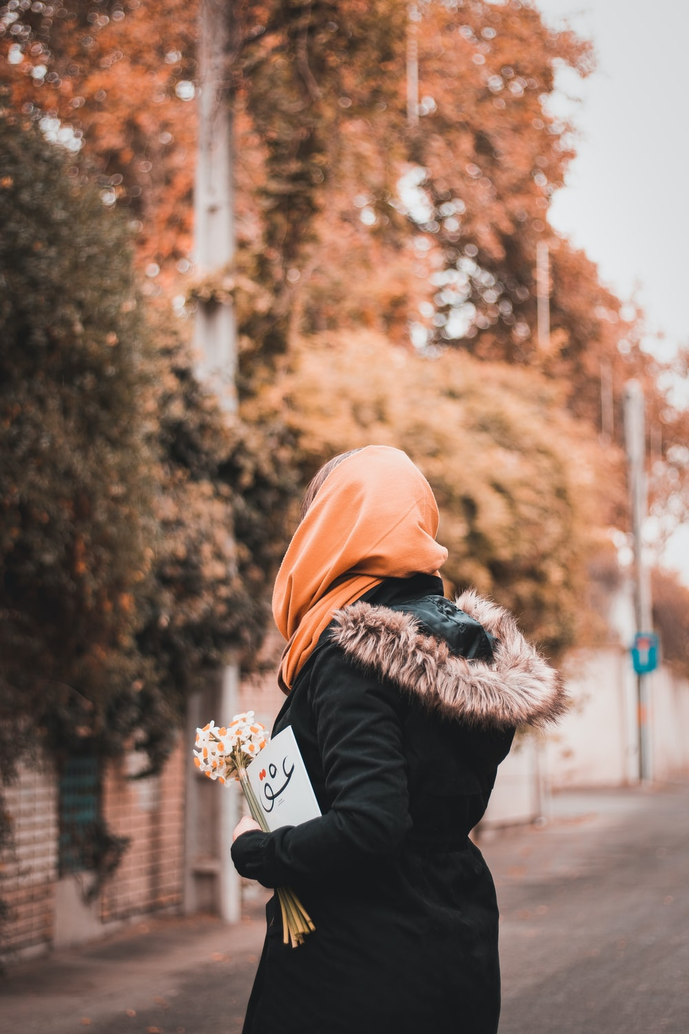woman in black jacket and brown knit cap carrying baby in black jacket