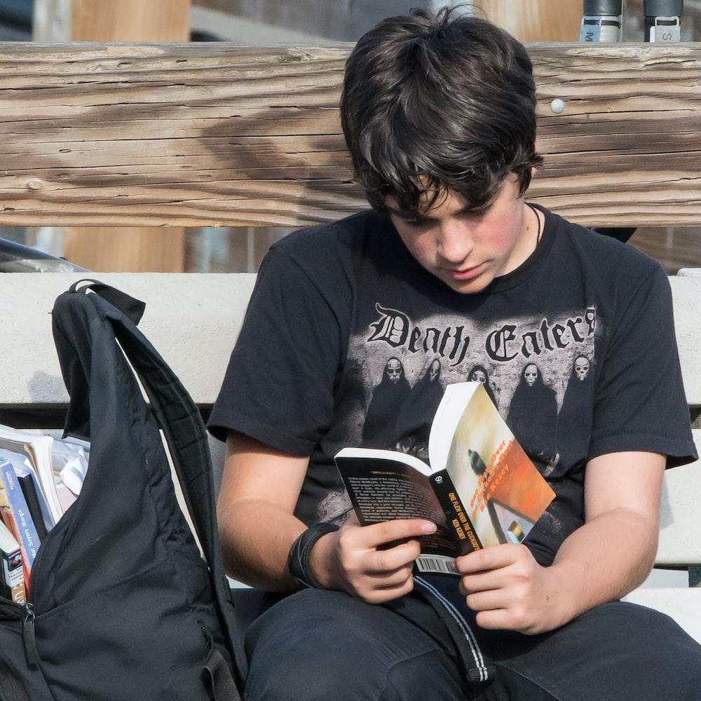 man in black crew neck t-shirt sitting on black chair
