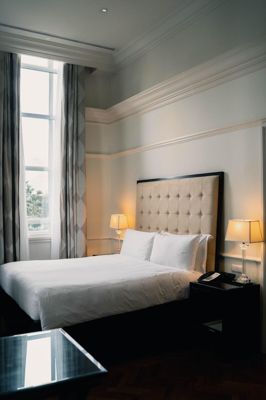 white bed linen near black wooden nightstand