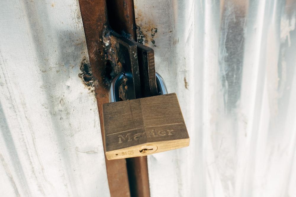 brown padlock on brown wooden post