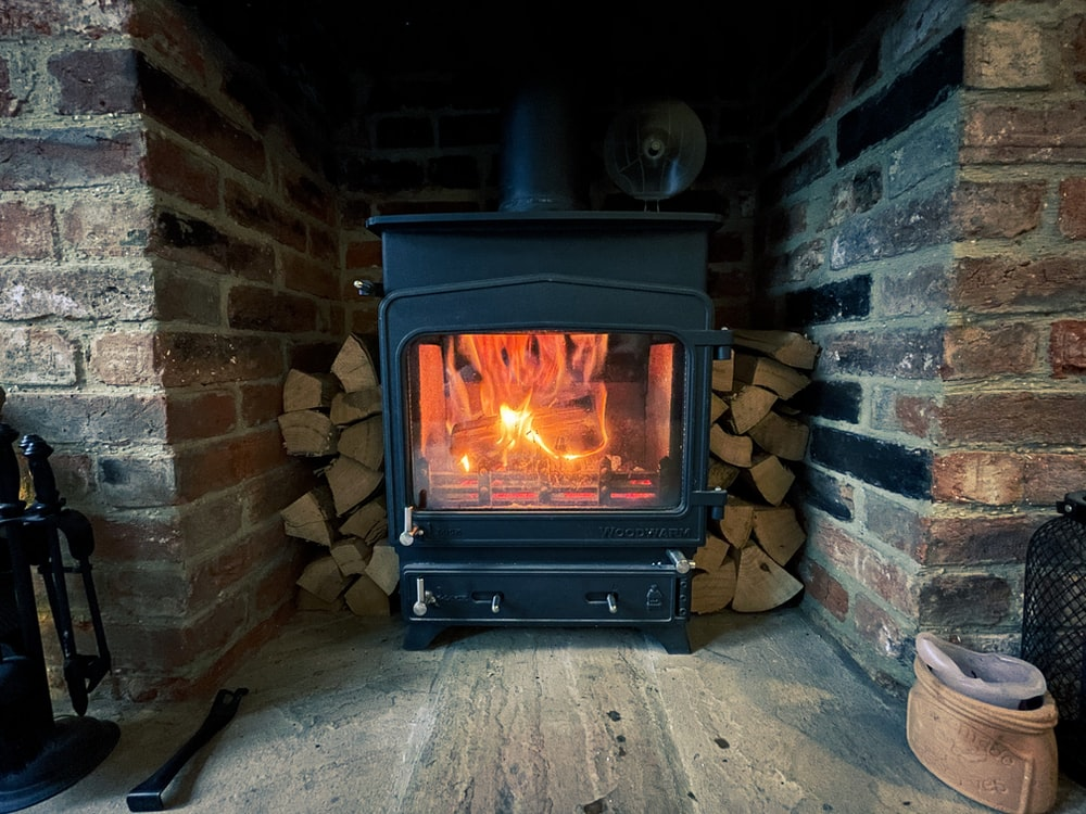 black wood burner near brown brick wall