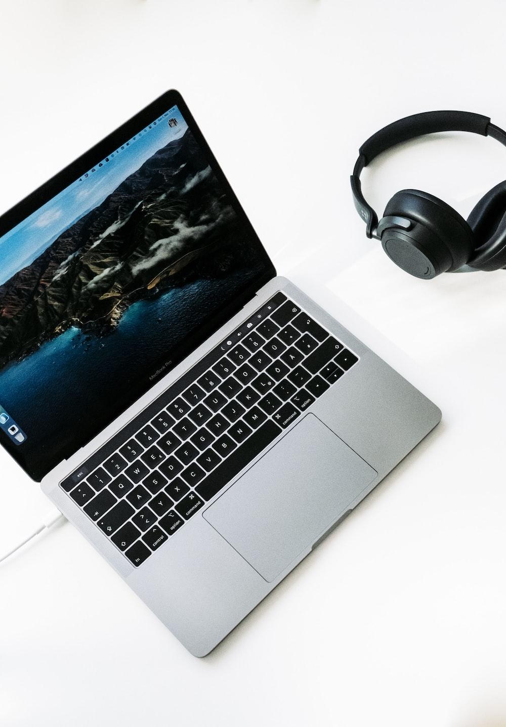 macbook pro beside black headphones