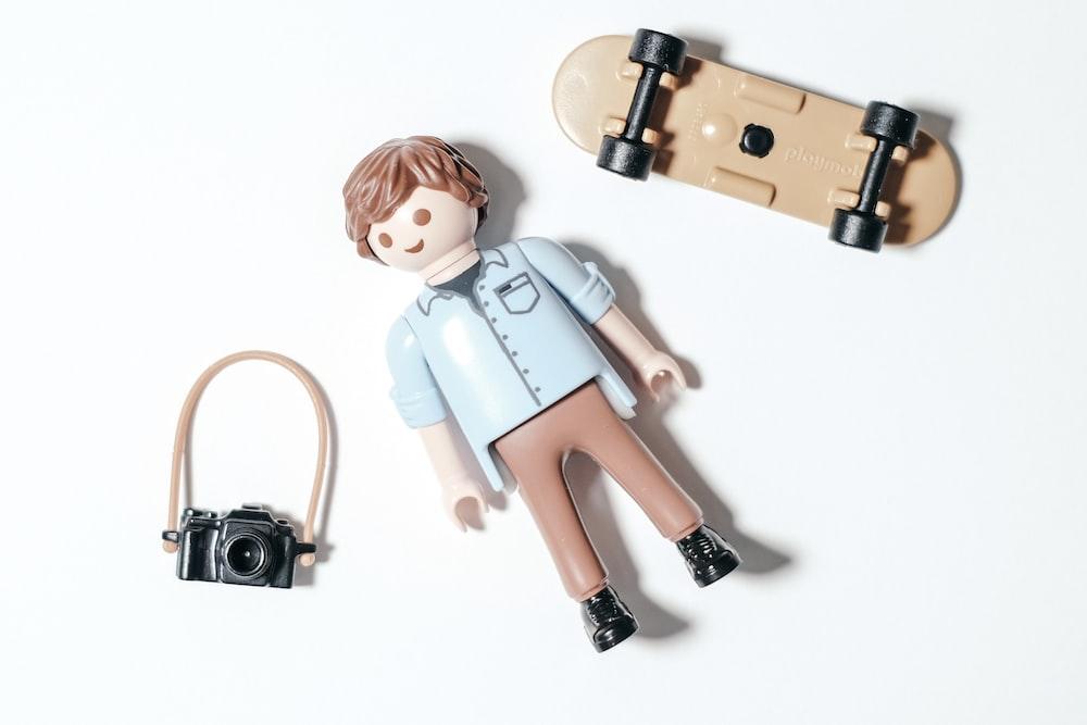 girl in blue dress holding camera figurine