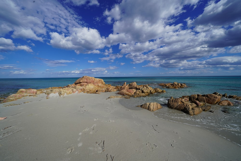 brown rocks on seashore under blue sky and white clouds during daytime