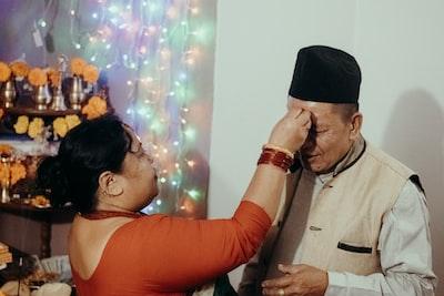 man in black hat kissing woman in orange tank top deepavali teams background