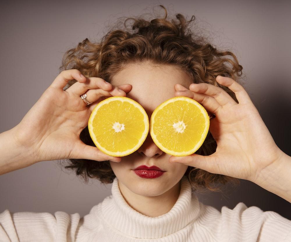woman holding sliced orange fruit