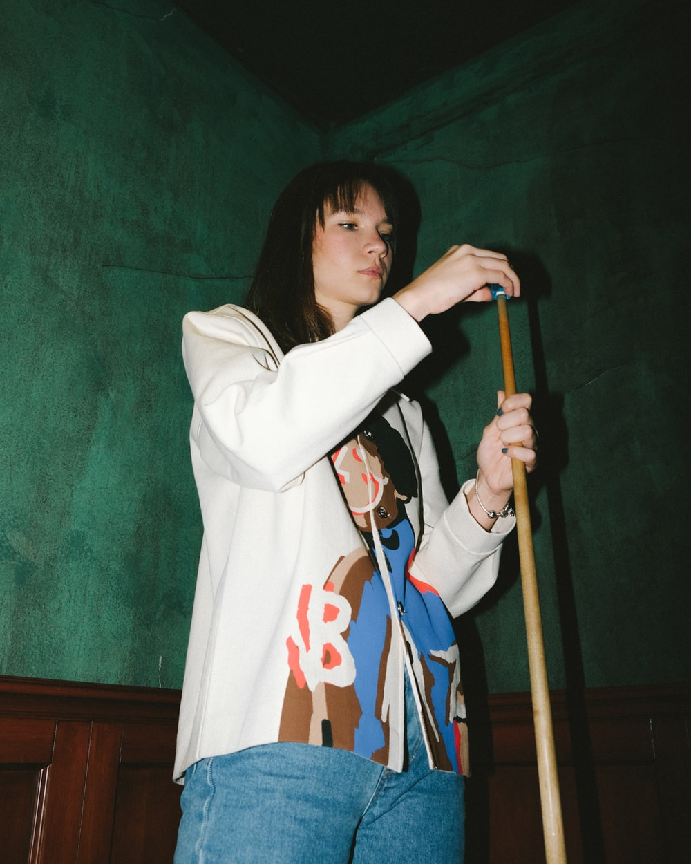 woman in white long sleeve shirt holding brown wooden stick