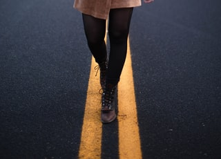 person in black leather boots standing on black asphalt road