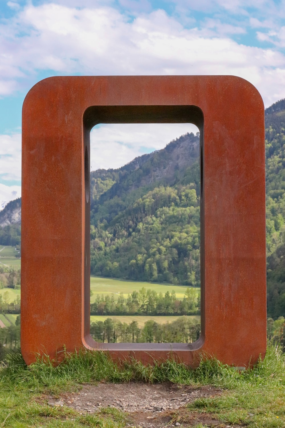 brown wooden frame with green trees in the distance