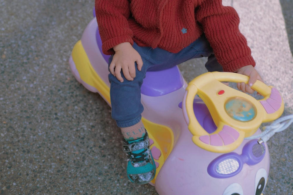 child in red sweater and blue pants sitting on yellow and green plastic toy