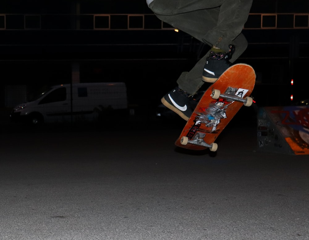 person in gray pants and black and orange sneakers riding orange skateboard