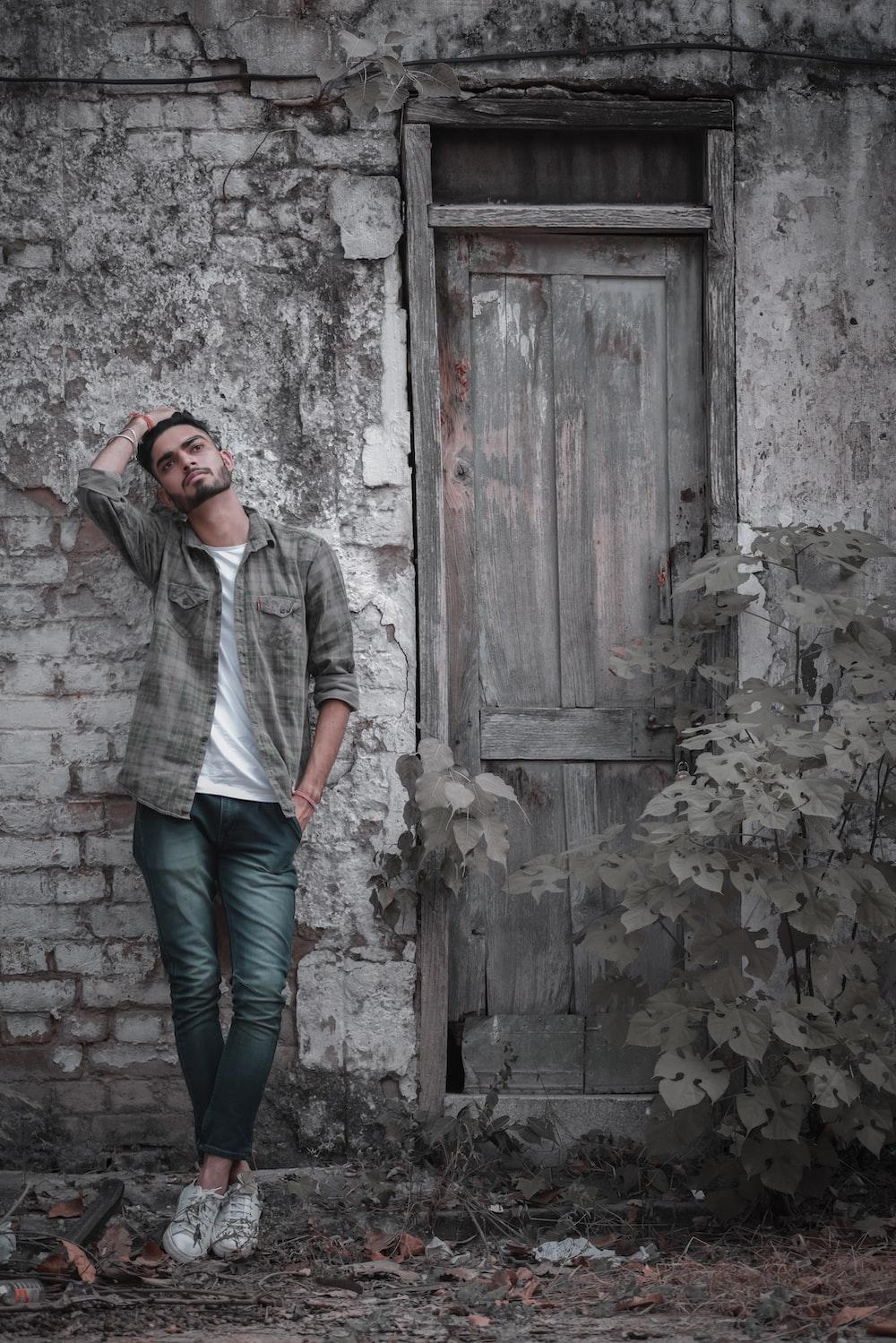 woman in gray jacket and blue denim jeans standing beside brown wooden door