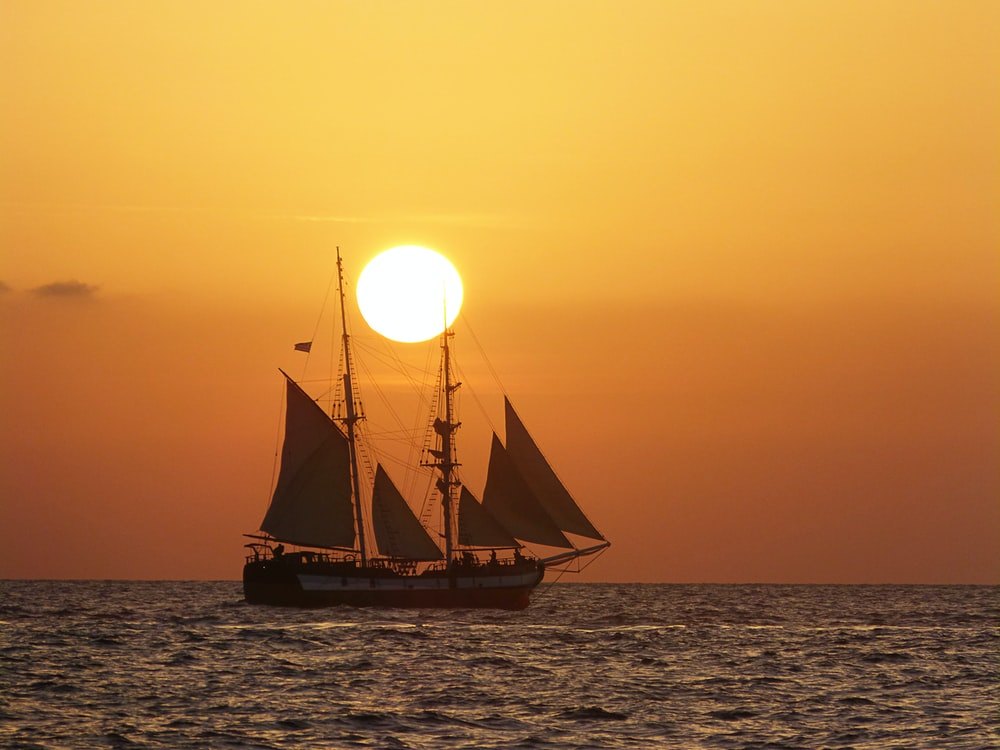 brown sail boat on sea during sunset