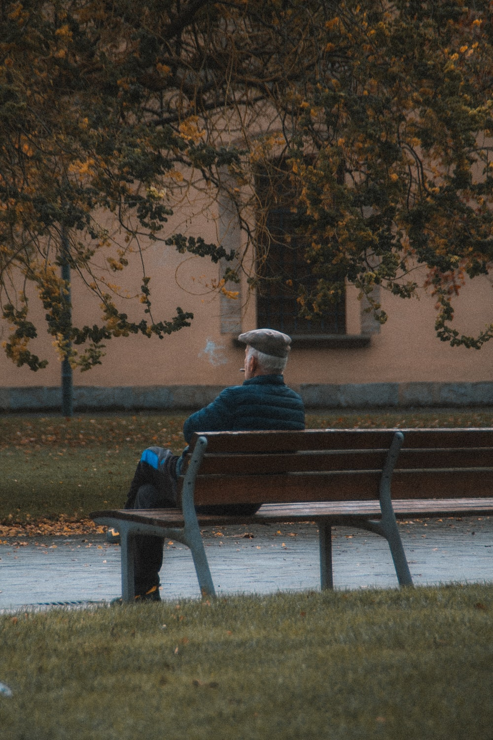 man in blue jacket sitting on brown wooden bench