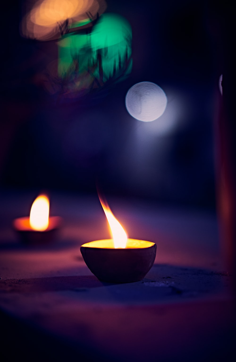 lighted candle in black round bowl
