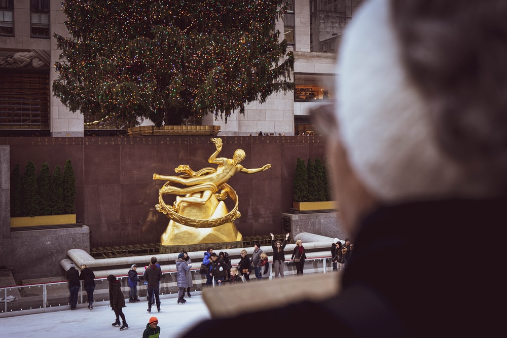 people standing in front of gold statue