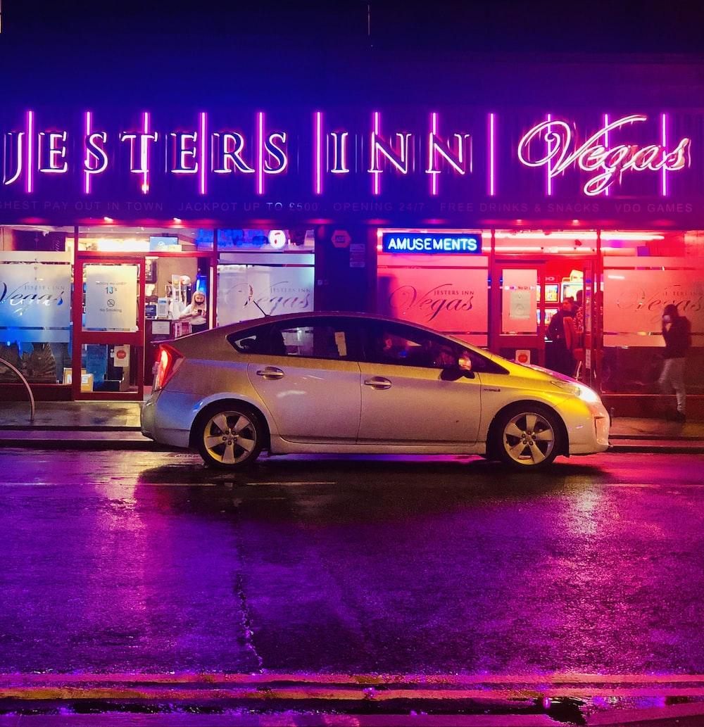 gold sedan on road during night time