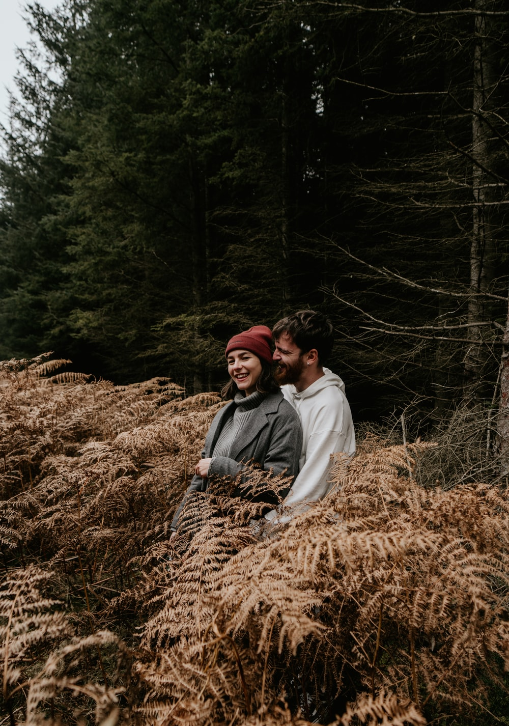 couple sitting on brown dried grass during daytime