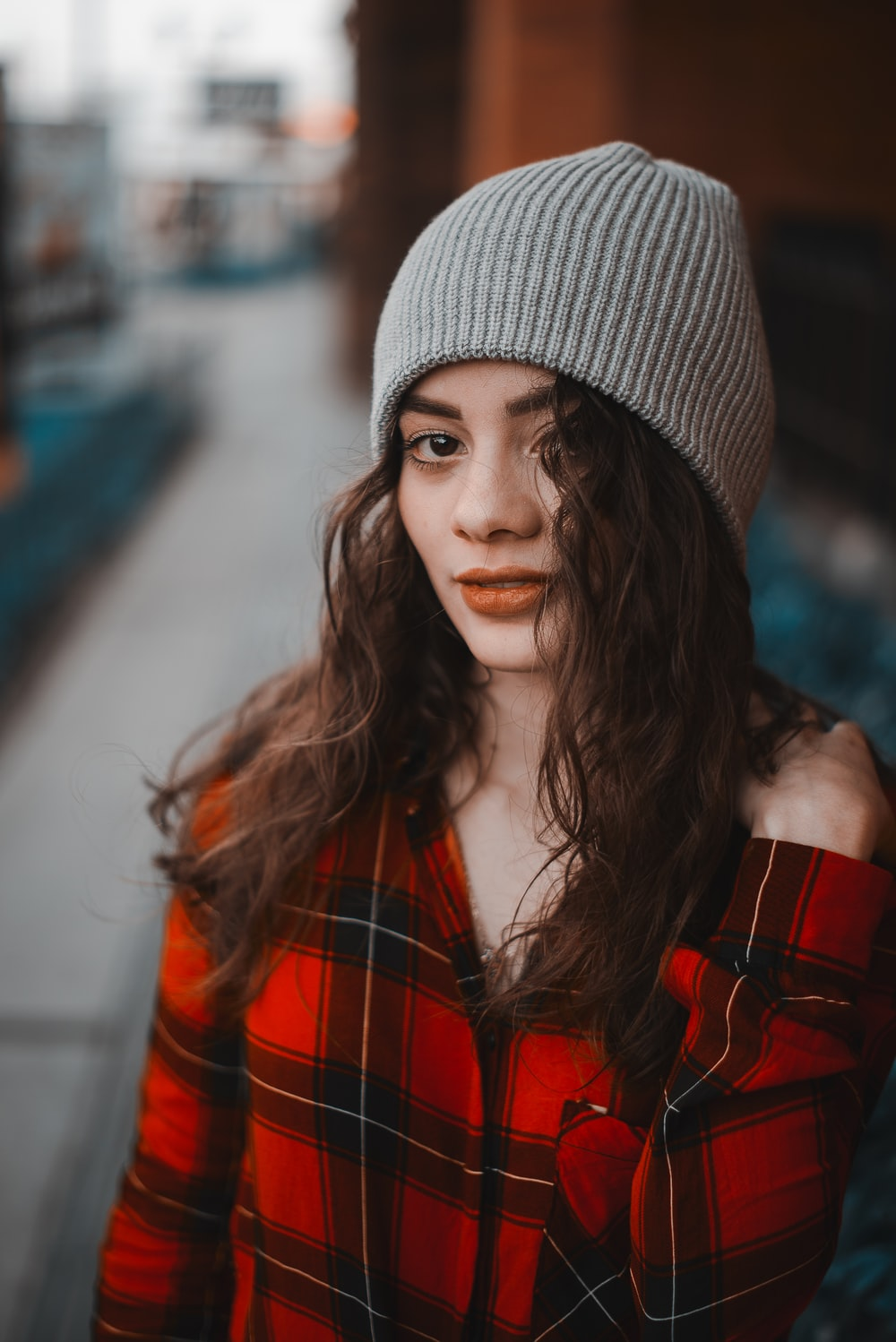 woman in red and black plaid jacket wearing gray knit cap