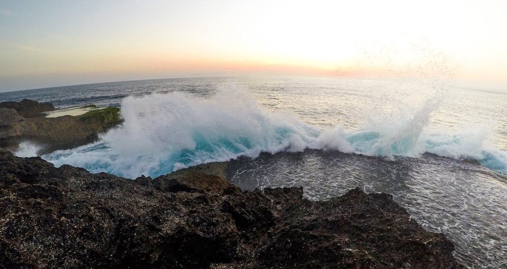 ocean waves crashing on black rock formation during daytime