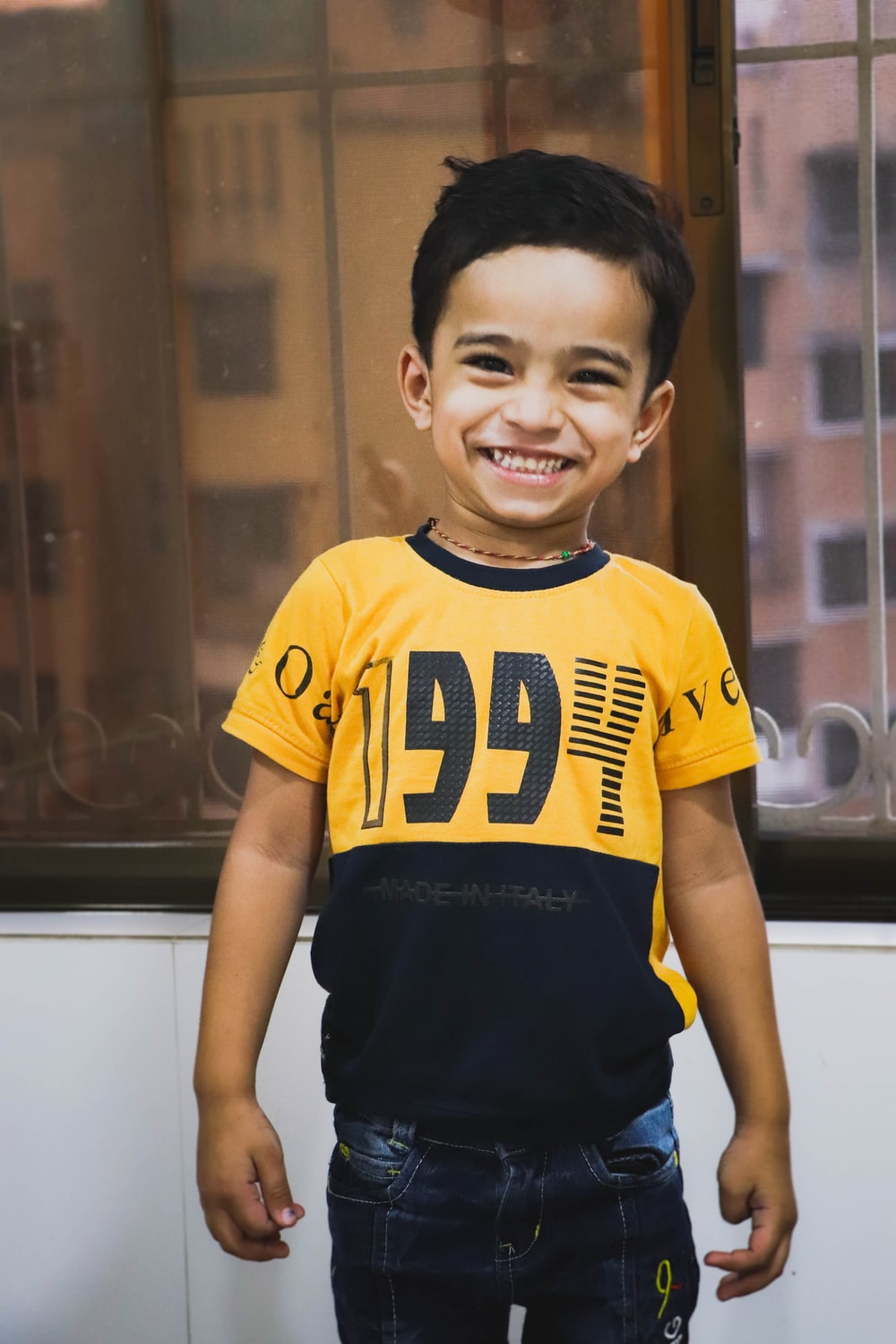 boy in yellow and black adidas crew neck t-shirt